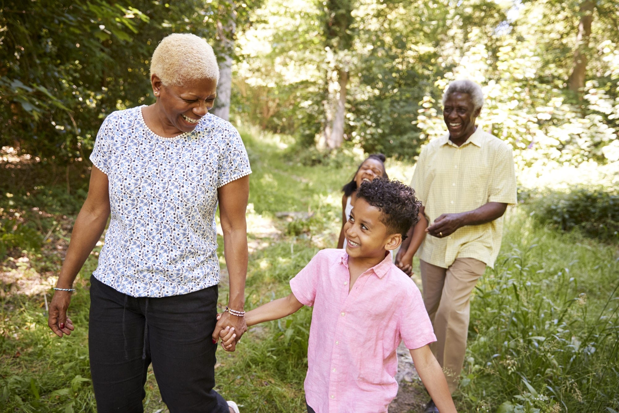 Black senior couple walking in forest with grandchildren