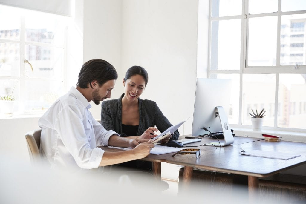 Man and woman at a desk in an office looking at documents